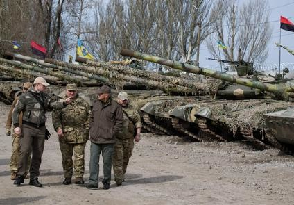 epa05246608 Ukrainian officers walk past a tank line of volunteers' 'Azov' battalion in the Urzuf village near of Maiupol, Ukraine, 06 April 2016. At least 1.2 million people have reportedly been relocated from the temporarily occupied territories of Donbass to other regions in Ukraine since the beginning of the conflict in the east of Ukraine in April 2014, Ukrainian media reported.  EPA/SERGEY VAGANOV